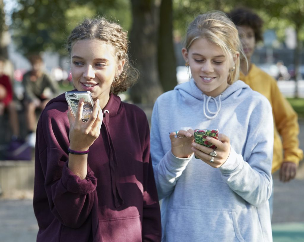 teenagers with hearing aids on phones